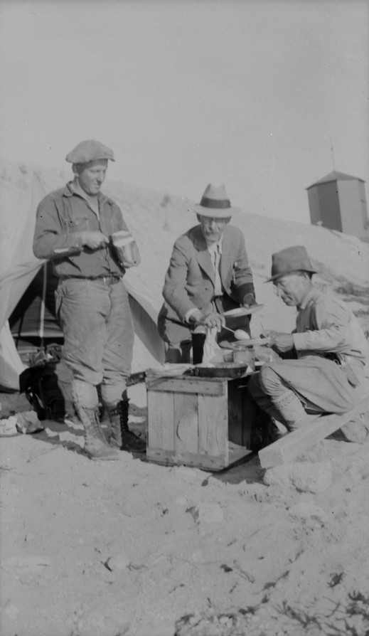 A black-and-white photograph of three men starting an outdoor breakfast. The men are positioned around a wooden crate with food on top of it.