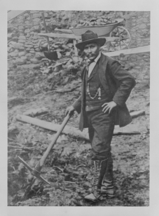 A black-and-white photograph of a man holding some prospecting equipment with one hand and the other hand on his hip looking directly at the viewer. Behind him is a loaded wheelbarrow.