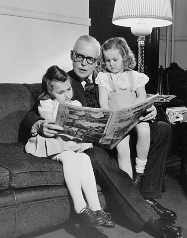 Black-and-white photograph showing Louis St-Laurent seated on a couch, reading a newspaper to two young girls sitting on either side of him.