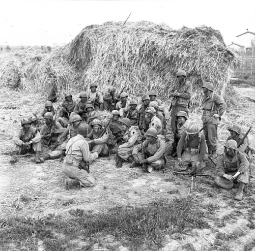 A black-and-white photograph of some two dozen soldiers sitting behind a large hay bale. The soldiers are being briefed before setting out on patrol.