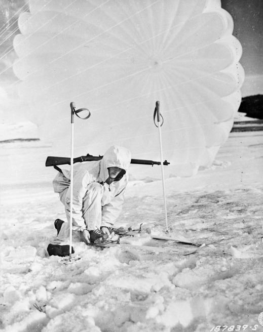 A black-and-white photograph of a soldier wearing white winter gear and crouching down to fix his ski bindings. A parachute is blowing in the wind behind him.