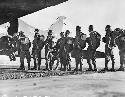 A black-and-white photograph of around a dozen soldiers wearing parachute gear, lined up to board a Douglas C-47 for training.