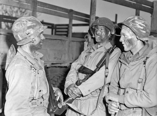 A black-and-white photograph of three soldiers with camouflage makeup preparing to go out on an evening patrol.
