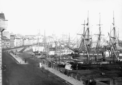 A black-and-white photograph of a busy harbour front, showing a street of buildings and boat-lined piers.