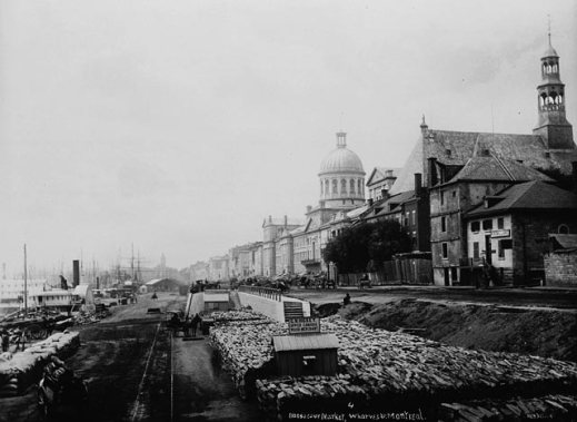 A black-and-white photograph of a wharf lined with various types of cargo with a large neo-classical building and a church along the shoreline.