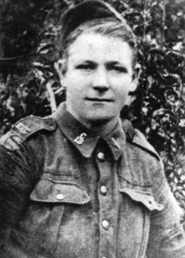 A candid black-and-white photograph of a soldier standing outdoors.