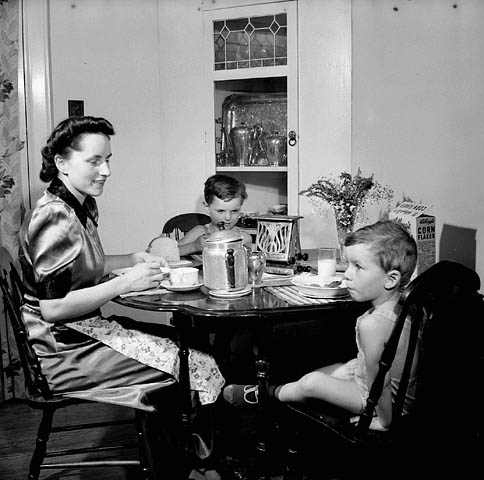 A black-and-white photograph of a woman and her two young sons sitting at a table eating breakfast.