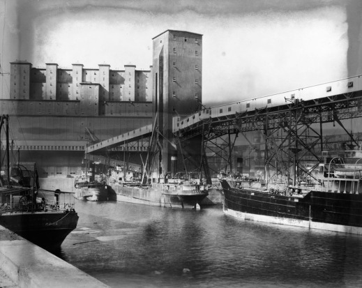 A black-and-white photograph of three moored ships. A port authority building is in the background. Along the wharf, there is a large unloading structure with hoists and scaffolding.