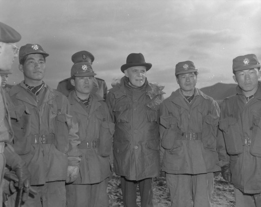 Black-and-white photograph of Louis St-Laurent flanked by soldiers. Two South Korean soldiers are on his left and two others on his right. Two Canadian soldiers can be seen in the background. In the foreground, on the left, is the partial profile of a Canadian soldier wearing glasses and a cap.