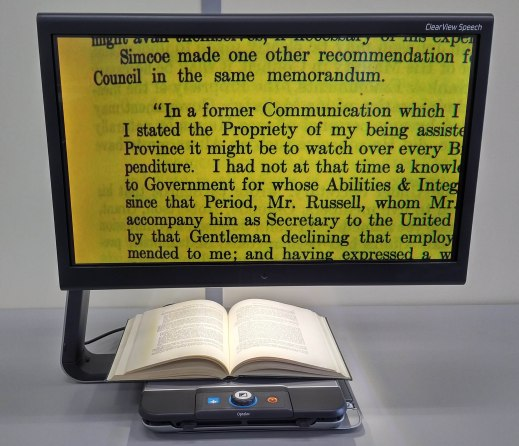 Colour photo of an assistive device having a moving tray with control buttons and an opened book laying on it. The monitor enlarges and displays the book text using a large black font on a yellow background.