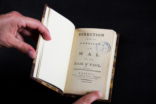 A colour photograph of a book open to the title page. It reads: Direction pour la guerison du mal de la Baie St Paul. A Quebec : Chez Guillaume Brown, au milieu de la grande cote. M, DCC, LXXXV.