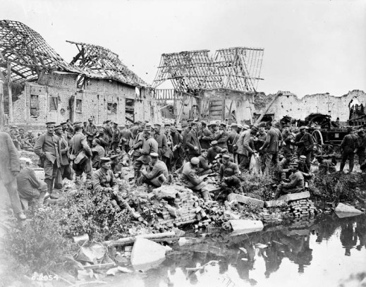 A black-and-white photograph showing a large group of German soldiers milling around between a village and a river or canal. The buildings in the background are mostly destroyed.