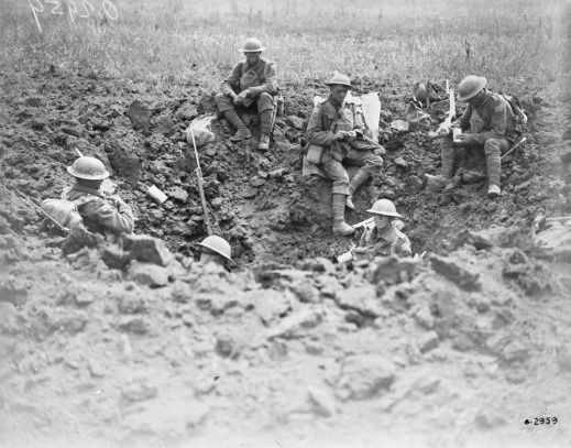 A black-and-white photograph of six soldiers wearing helmets sitting in a large hole in the mud. Some are eating, while others are holding guns and facing away from the camera.