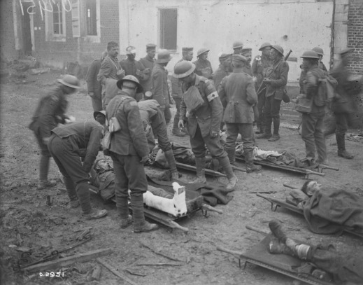 A black-and-white photograph of stretcher-bearers and medical personnel caring for wounded soldiers while other soldiers are standing around in the background.