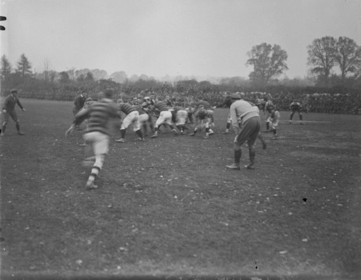 A black-and-white photograph of two rugby teams in a scrum for the ball. Two referees watch the play unfold.