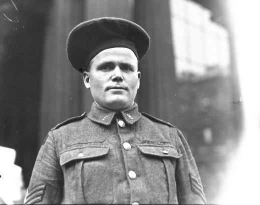 A black-and-white photograph of a soldier in uniform looking straight at the camera and wearing a large beret.