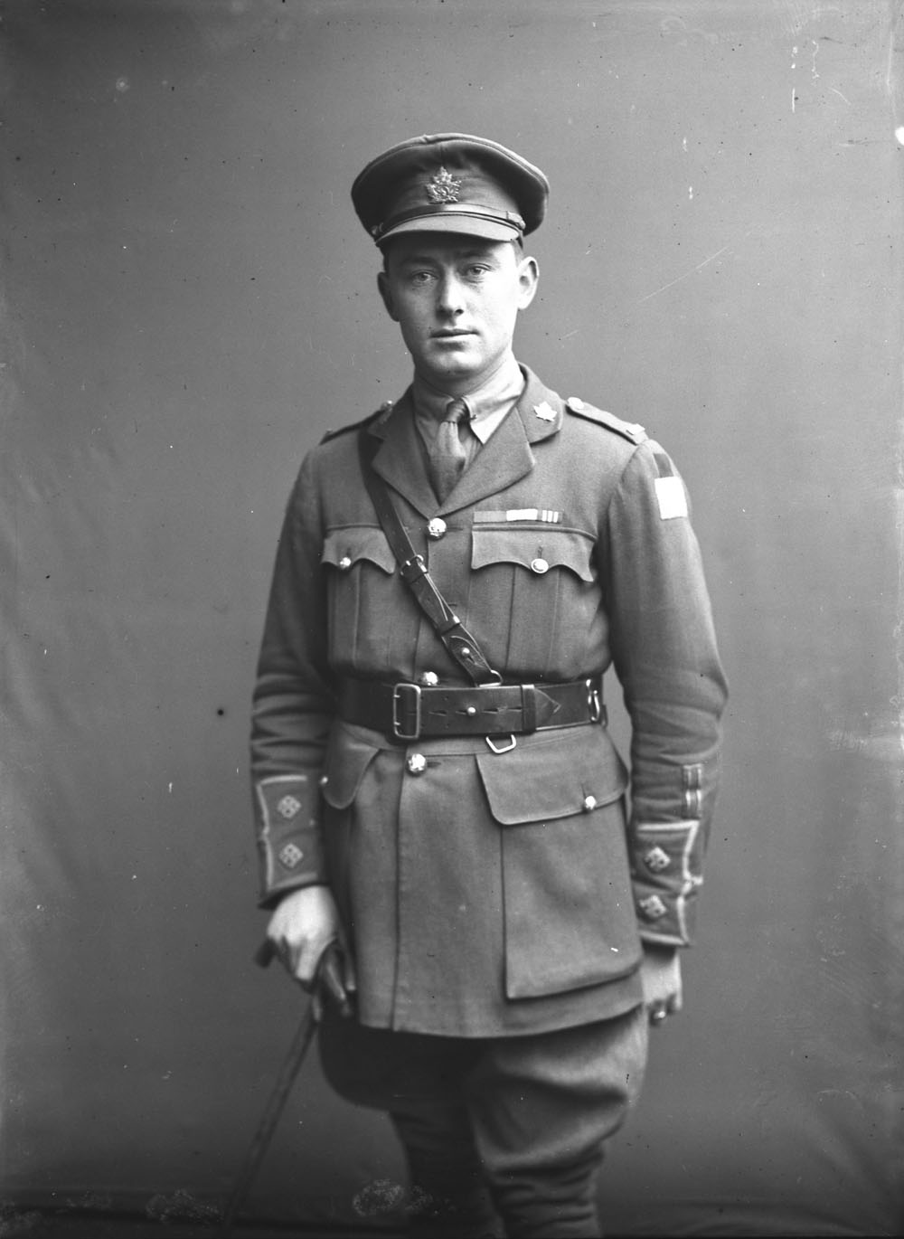 A black-and-white photograph of a military officer standing with a cane.