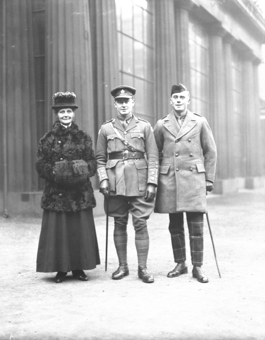 A black-and-white photograph of three people standing and posing for a photograph: a woman in a fur coat, a military officer with a cane, and a soldier with a cane and beret.
