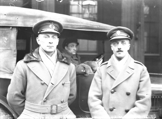 A black-and-white photograph of two officers standing in front of a car in which a driver is seated. They both wear officers' caps and greatcoats.