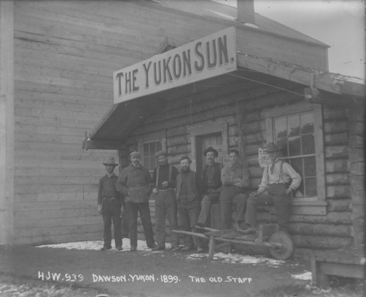 A black-and-white photograph of a group of men standing in front of a log building with a sign that reads The Yukon Sun.