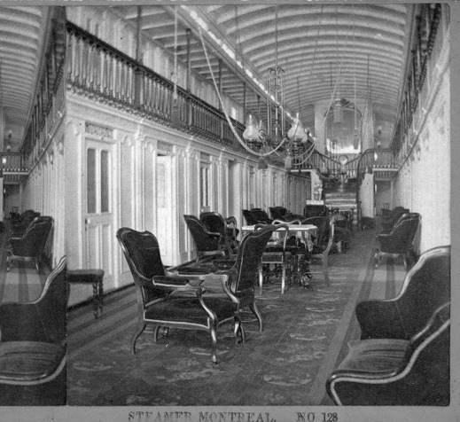 A black-and-white photograph of the interior of the steamer Montreal, showing a large carpeted sitting room with numerous cushioned chairs.