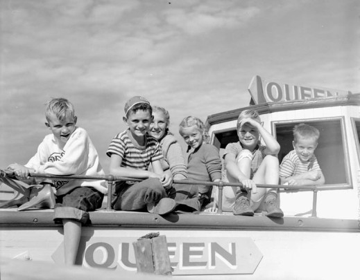A black-and-white photograph of two girls and four boys sitting on the foredeck of the motorboat Queen.