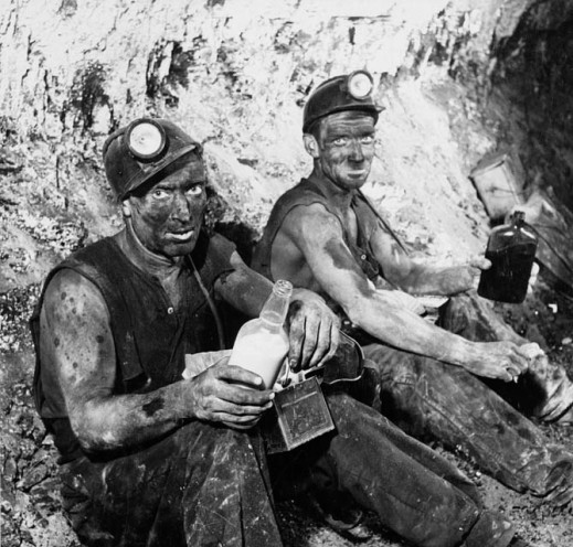 A black-and-white photograph of two men sitting in a tunnel, covered in dust, wearing mining safety equipment eating lunch.