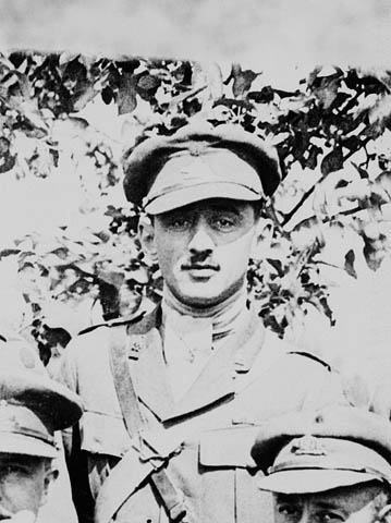 A black-and-white photograph of a soldier in uniform looking straight at the camera. He is standing behind two other men in uniform whose faces are partially visible in the foreground. There is a tree in the background.