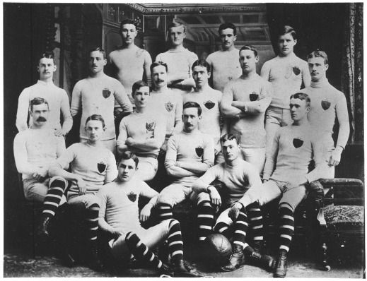 A black-and-white photograph of the McGill University rugby team, 1884-1885. James Naismith sits with his teammates (far-left of the second row of four).