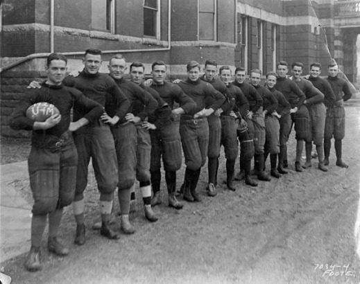 A black-and-white photograph of the Senior University Rugby Team, Ontario. The members stand in a row at an angle with their left hands on their hips, and their right hands on the right shoulder of the person in front of them.
