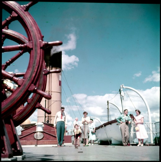 A colour photograph of a boy playing shuffleboard, watched by a man and a woman on the Canadian Pacific Railway cruise ship Assiniboia.