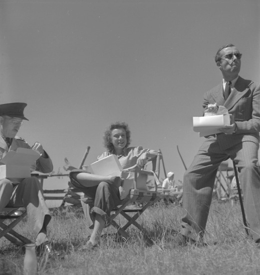 "A black-and-white photograph of actor Lucia Carroll and two cast members sitting outside eating lunch on the film set of ""Captain In the Clouds""."