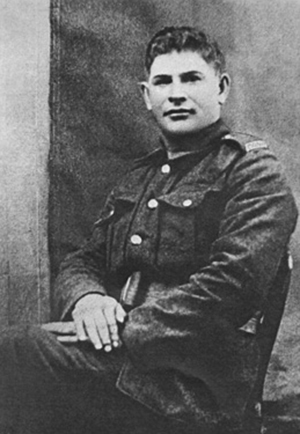 Black-and-white photograph of a solider in uniform sitting in a chair with his hands crossed and looking at the camera.