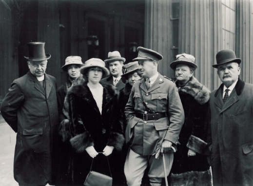 A black-and-white photograph of four women and four men wearing heavy coats and hats in front of Buckingham Palace. The man in the middle is wearing a military uniform and leaning on a cane.