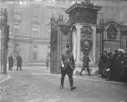 A black-and-white photograph of a mustachioed man wearing tartan pants, a Sam Brown belt and a cap walking with a walking stick through ornate gates. A crowd on the right is looking toward the gates.