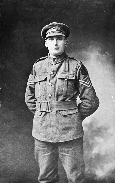 A black-and-white studio photograph of a soldier standing with his hands behind his back.