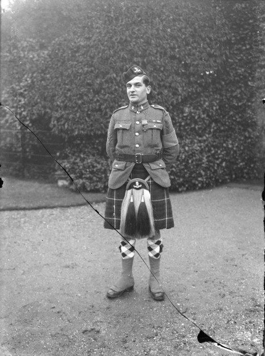 A black-and-white photograph of a standing soldier wearing a kilt.