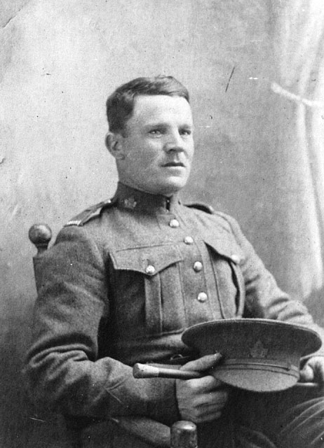 A black-and-white portrait photograph of a seated soldier who holds his cap and swagger stick on his lap.
