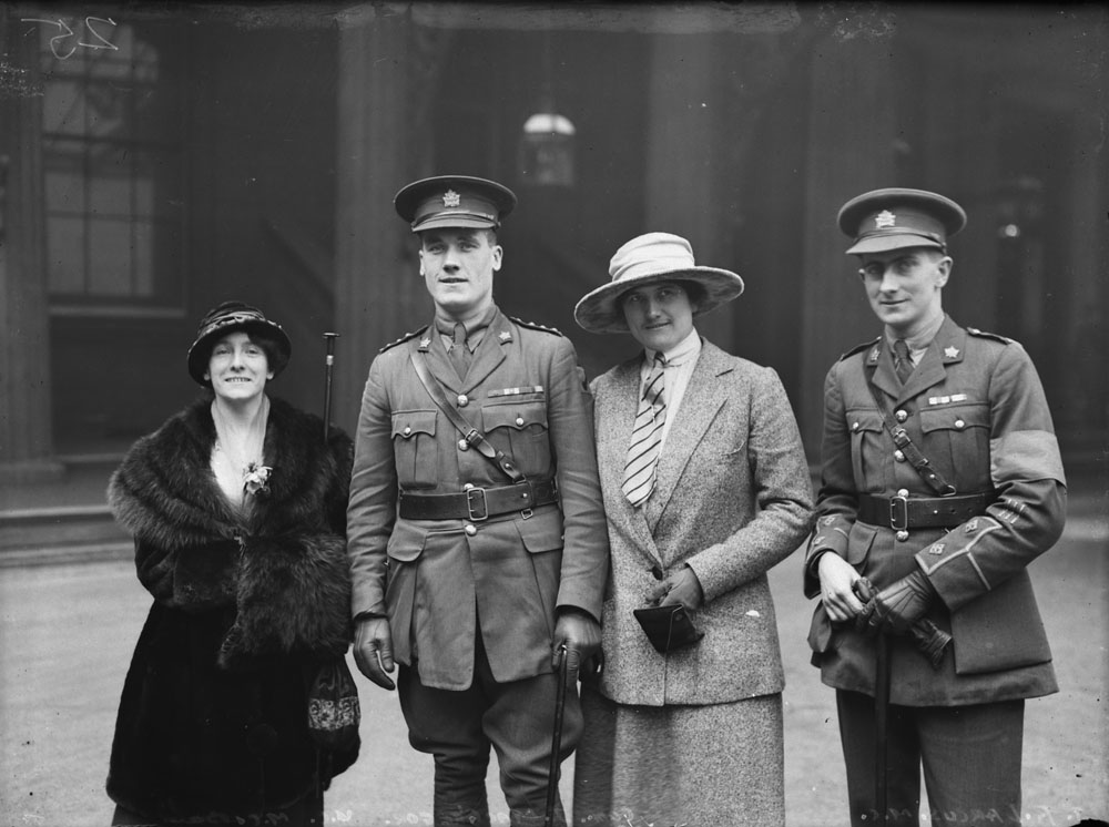 A black-and-white photograph of four people standing and looking toward the camera.