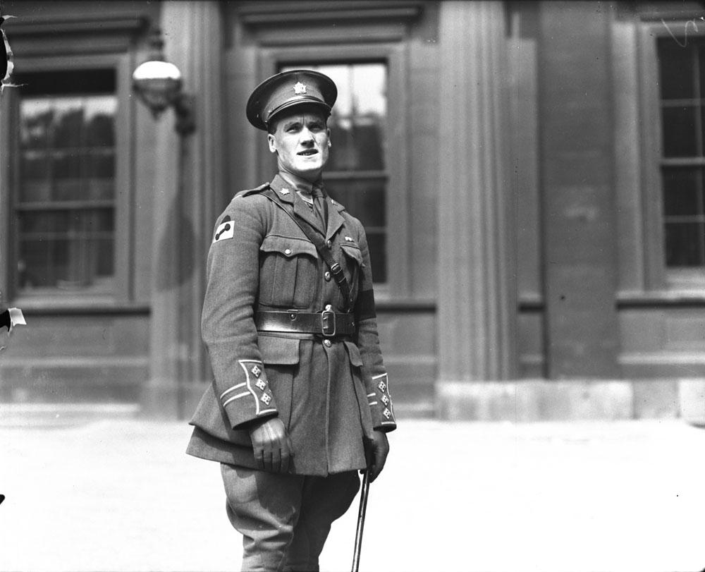 A black-and-white photograph of a soldier in service dress uniform, squinting in the sun and turned slightly away from the camera.