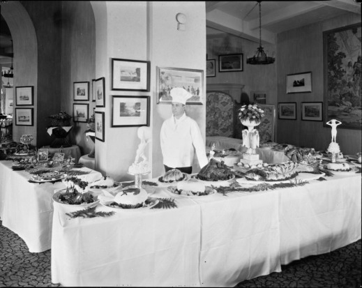 A black-and-white photograph of a formal dinner-buffet setting of three tables staffed by a chef wearing a white coat and hat.