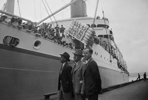 A black-and-white photograph of three men standing in front of a ship.