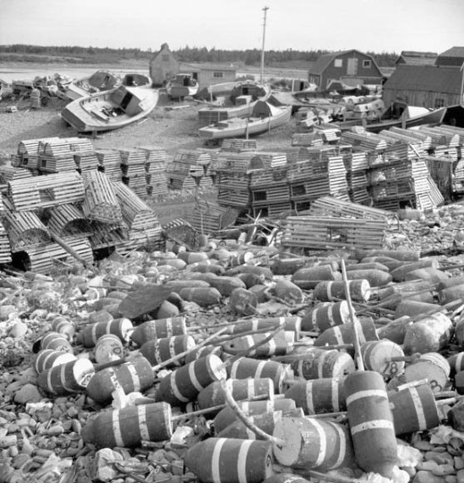 A black-and-white photograph of a coastal village, with lobster boats in the background, lobster pots in the middle distance, and floating markers in the foreground.