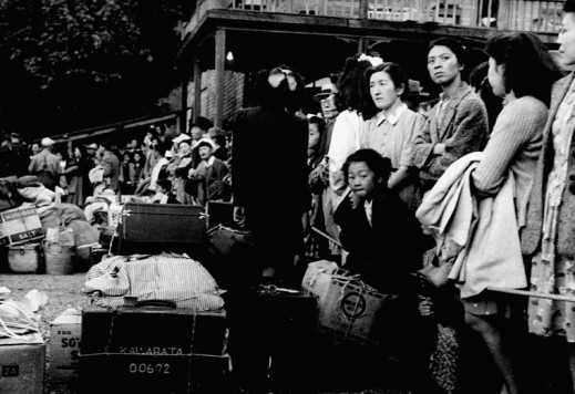 A black-and-white photograph of a group of women with a child standing in front of luggage and crates.