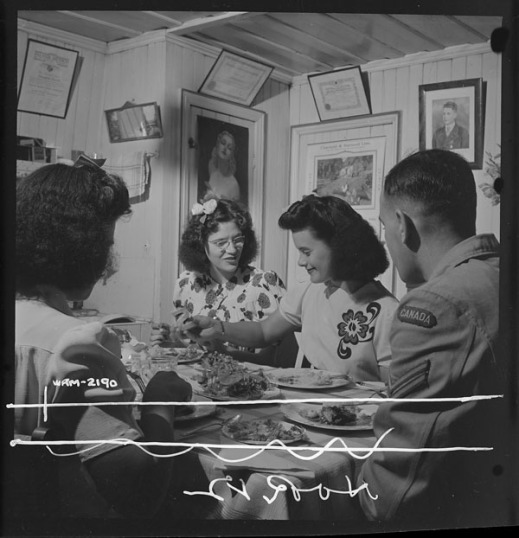 A black-and-white photograph of three women and a man eating dinner at home in the dining room.