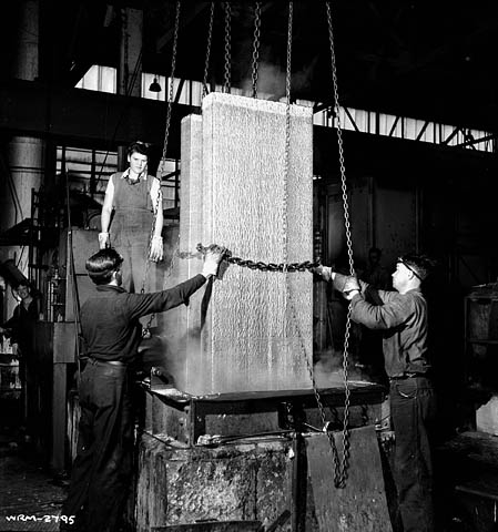A black-and-white photograph of a woman and two men lifting and maneuvering aluminum blocks with chains out of moulds.