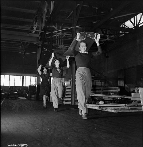 A black-and-white photograph of three women working in unison to carry a long sheet of aluminum over their heads to the inspection table.