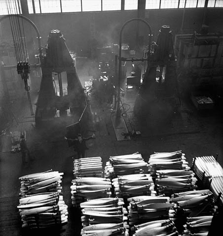 A black-and-white photograph providing an overhead view of an aluminum forge used to produce bomber propellers. There are several large pallets of propellers in the foreground.