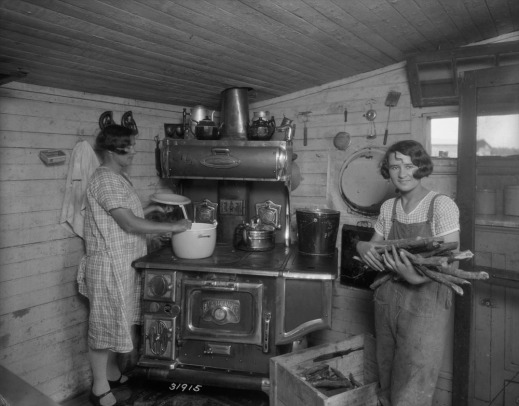 A black-and-white photograph of two women preparing dinner in a kitchen. On the left, one stirs food in a pot on a wood burning stove. To the right, one holds an armful of firewood.