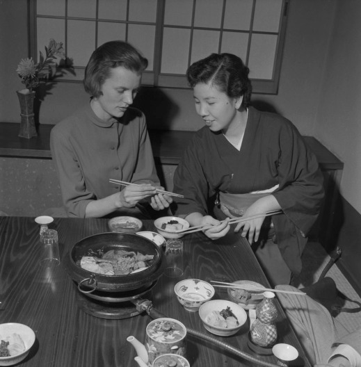 A black-and-white photograph of two women sitting in a Japanese restaurant with a variety of dishes on the table. The woman on the right instructs the one on the left how to use chopsticks.